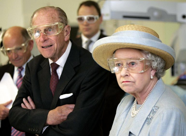 Queen Elizabeth II and the Duke of Edinburgh wearing safety glasses during a laser surgery demonstration at the University College Hospital, London. October 2005.