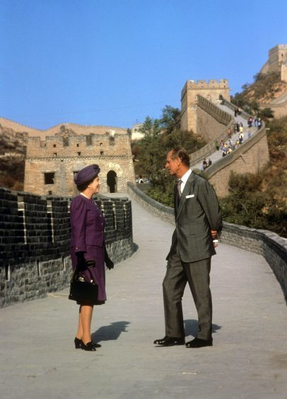 Queen Elizabeth II and the Duke of Edinburgh on the Great Wall of China at the Bedaling Pass, 50 miles north-west of Beijing, on the third day of their State Visit to the country. October 1986.