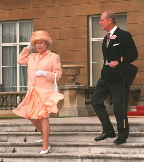 Queen Elizabeth II and the Duke of Edinburgh descending the steps of Buckingham Palace at a garden party. July 1998.