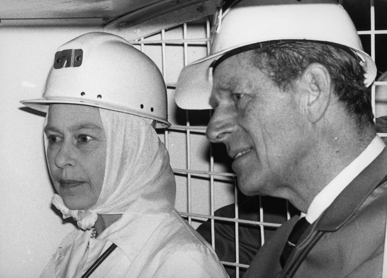 Queen Elizabeth II and the Duke of Edinburgh seated in a haulage truck to go down to the lower level of the Geevor tin mine at Pendeen, Cornwall. November 1980