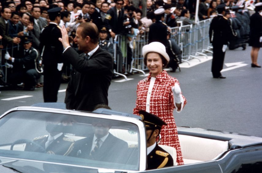 Queen Elizabeth II and the Duke of Edinburgh in an open top car during their State visit to Japan. May 1975.