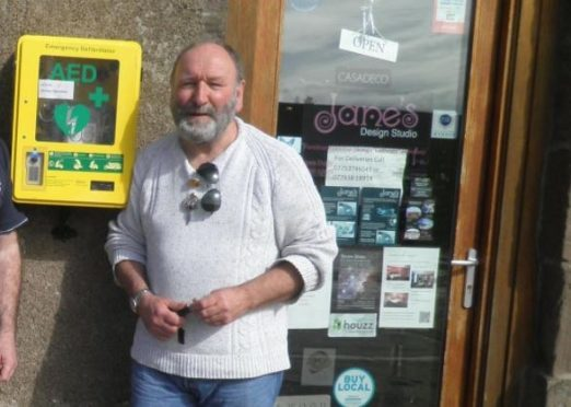 Phil Mills-Bishop pictured next to the harbour defibrillator shortly after its installation