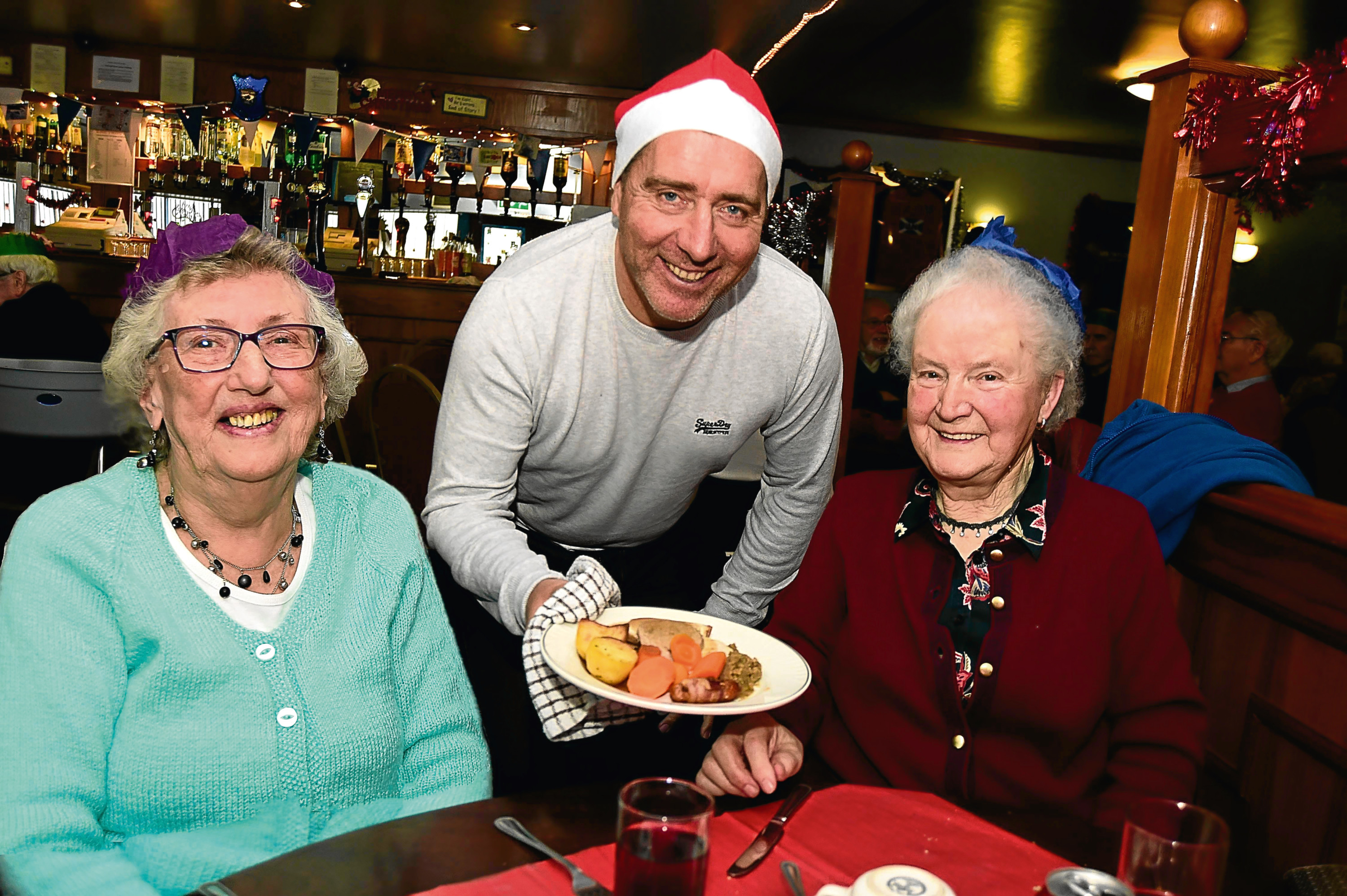 PETERHEAD FC MANAGER JIM MCINALLY SERVES UP THE TURKEY TO ELEANOR WALKER (L) AND DAISY DUNCAN AT THE BALMOOR CHRISTMAS LUNCH FOR LONELY PEOPLE.