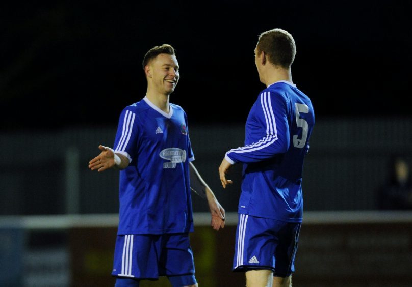 Cove's Mitch Megginson celebrating scoring his 2nd goal to put his side 4-0 ahead with Eric Watson.