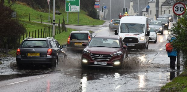 Traffic carefully makes its way through flooding on Fort William's North Road