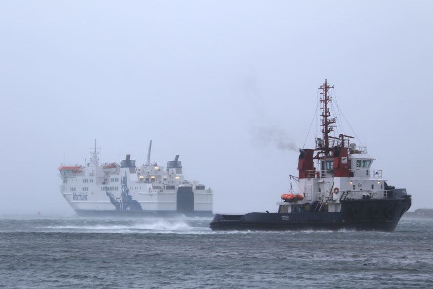 The MV Hamnavoe, escorted by an Orkney tug heading back out  to Scapa Flow for shelter after trying to berth at Stromness Pier.