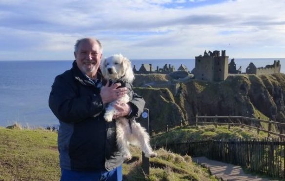 Thai the therapy dog and owner David Neill at Dunnottar Castle.