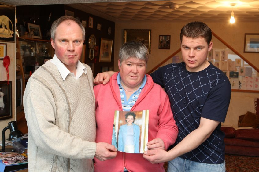The Aim family from left Brian, Peggy and brother Allan holding a photograph of Karen.