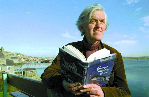 "George Mackay Brown with his book ""Beside the Ocean of Time""."