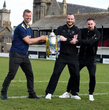 Rangers legend Arthur Numan wrestles Fraserburgh's Ryan Christie and Marc Dickson for the cup.