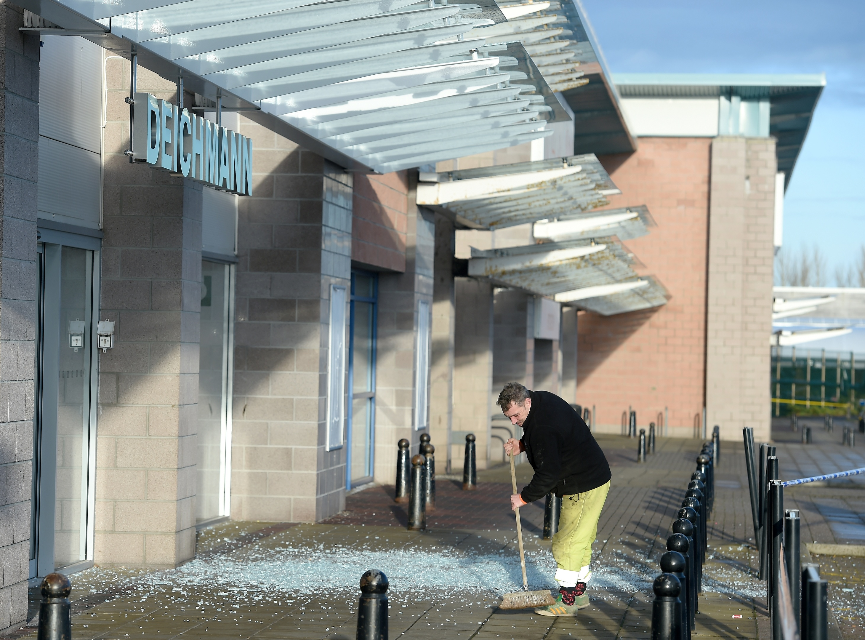 The clear-up begins following the overnight shattering of a pane of glass above the pedestrian walkway. Picture by Sandy McCook.
