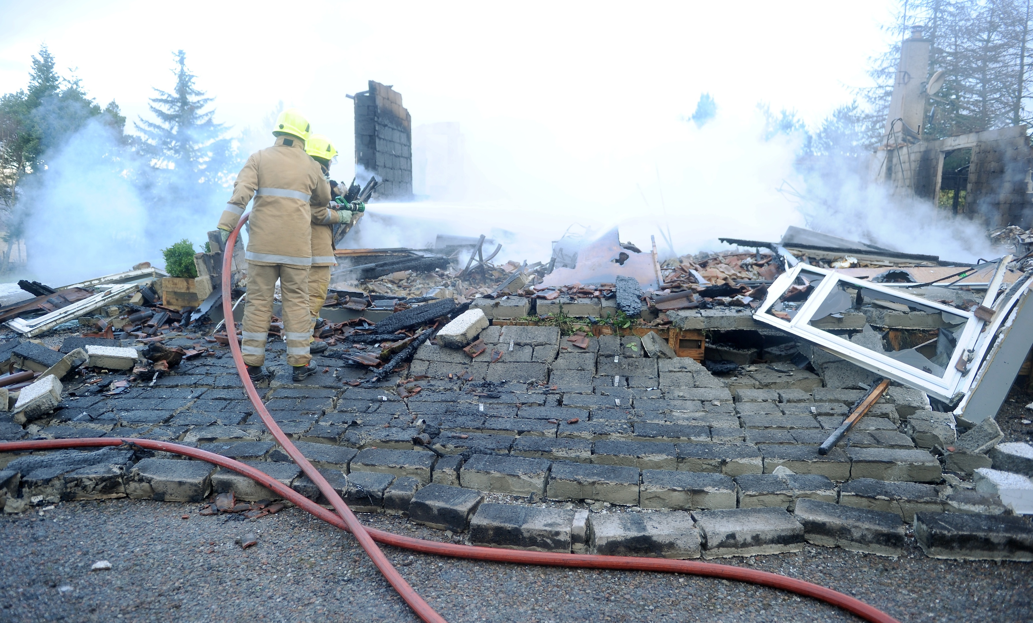 Firefighters continue to extinguish the fire which destroyed a house in the Foxhole area of Kiltarlity. Picture by Sandy McCook