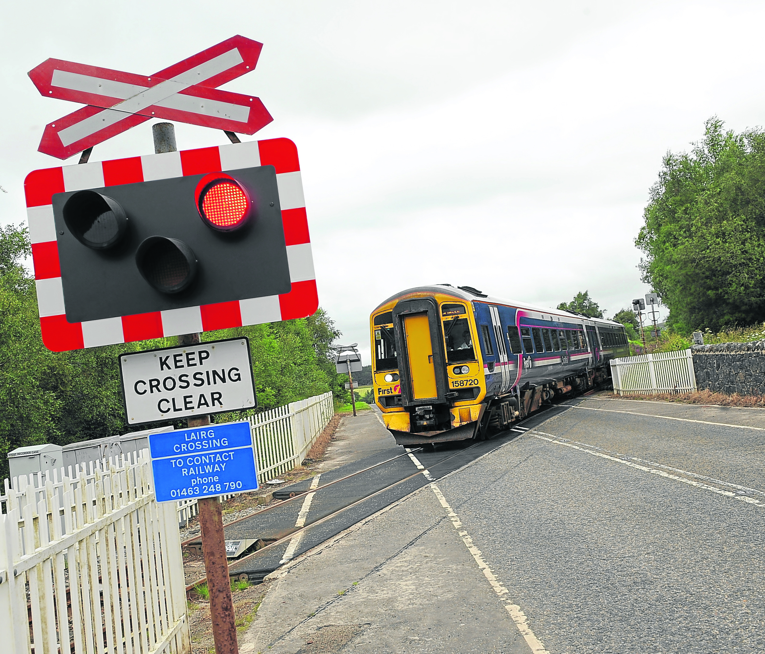 A southbound train crosses the Lairg automatic open level crossing