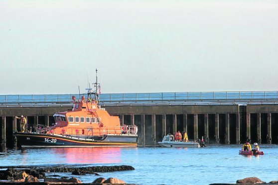 The Wick lifeboat, along with their small inflatable and another vessel search the harbour, near Scalesburn
