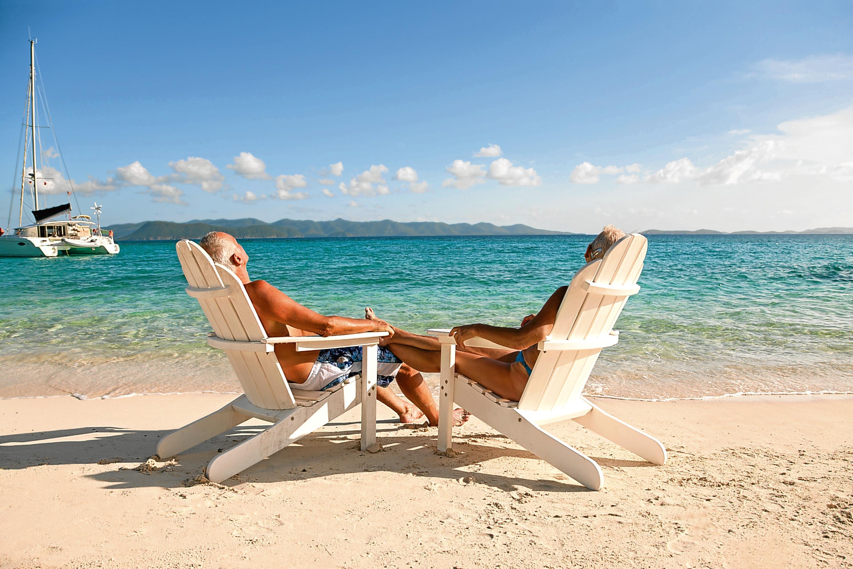 rear view of retired couple sunbathing in beach chairs at White Bay, Jost Van Dyke, British Virgin Islands