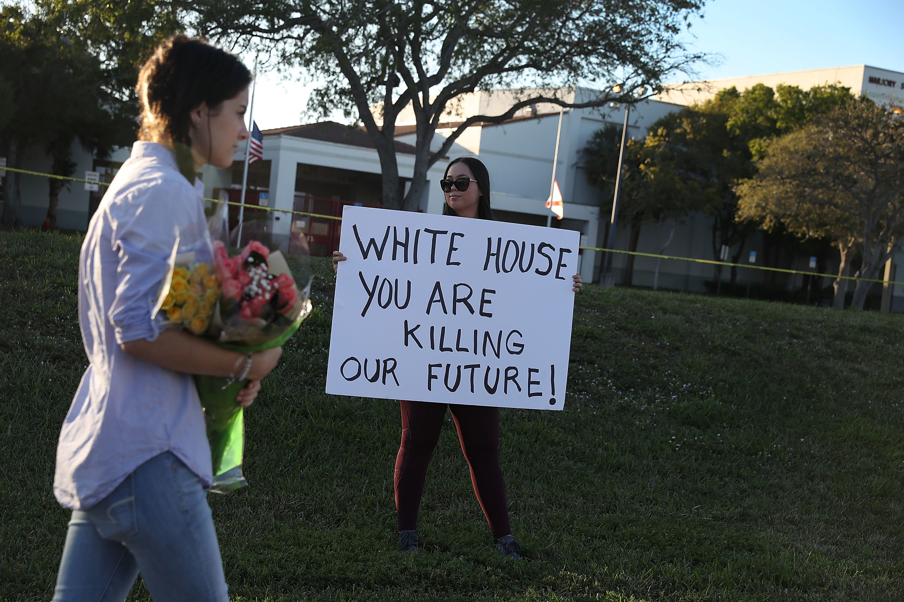 Karissa Saenz, a senior at Marjory Stoneman Douglas High School  holds a sign in Parkland, Florida. Police arrested and charged 19 year old former student Nikolas Cruz for the February 14 shooting that killed 17 people.  Photo by Joe Raedle/Getty Images.