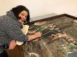 Artist Aneliya Beaton puts the damaged parts of the painting back together