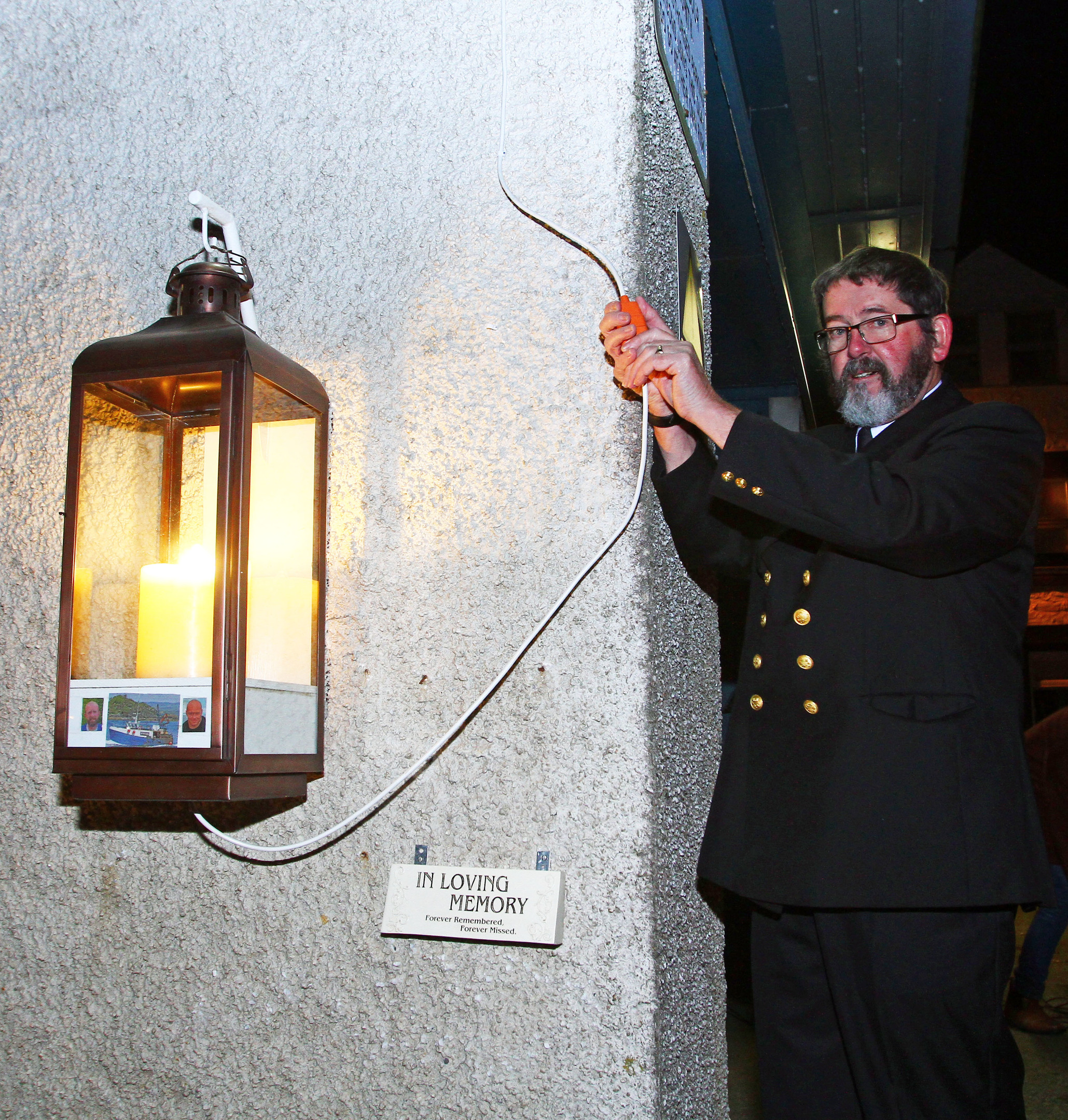 Matthew Ramsay, superintendent of the Fishermen's Mission performs the switching on of the candle at the vigil held on the quay in Tarbert.  Picture: Kevin McGlynn