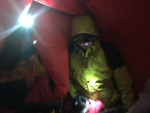 Casualty being assessed inside a bivvy bag. Pic credit: Cairngorm Mountain Rescue Team