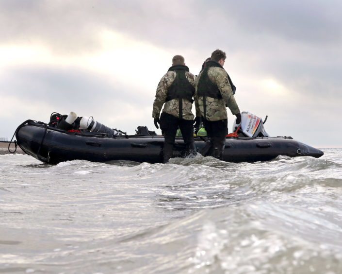 Divers launch the boat into the water.
