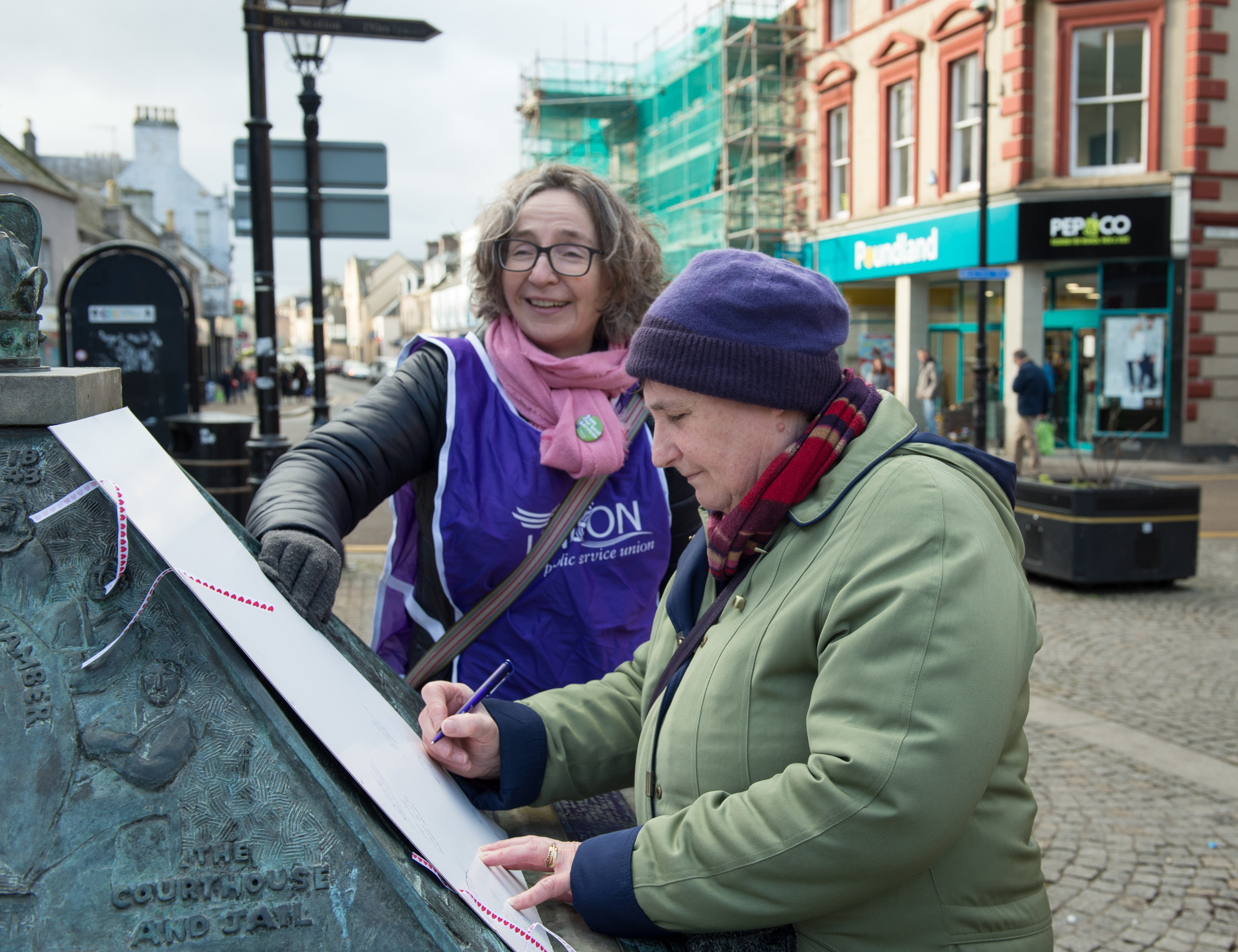 School librarian Angela Walker signs the Valentine's Day card with Unison member Eilidh Macleod.