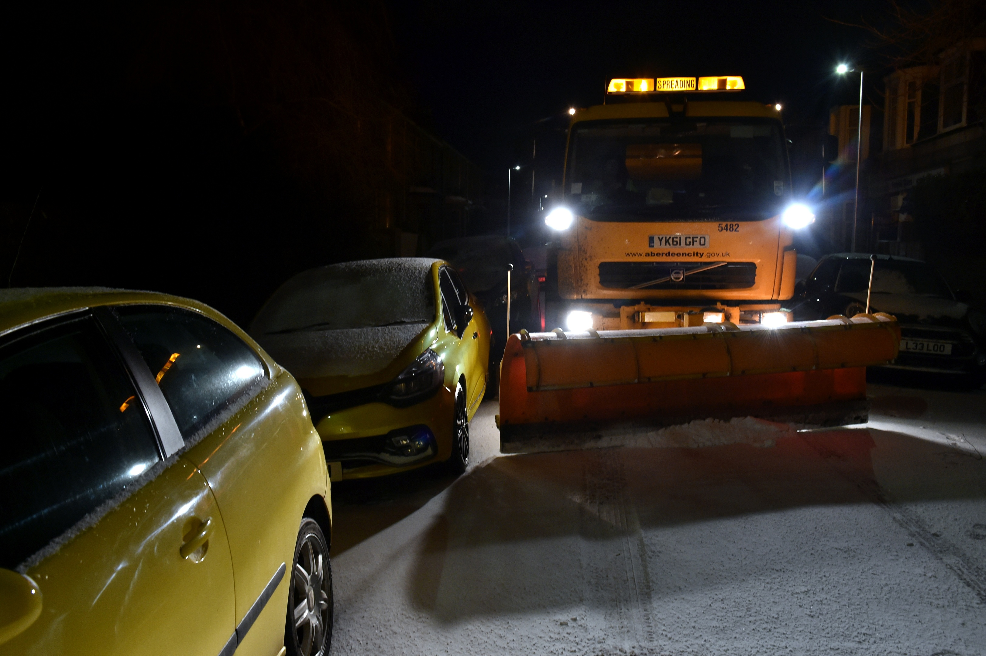 The Beast from the East snow storm arrived in Aberdeen. The gritter edges past badly parked cars.