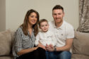 Pictured is Noel with his parents: Peterhead footballer Rory McAllister and wife Ashley.