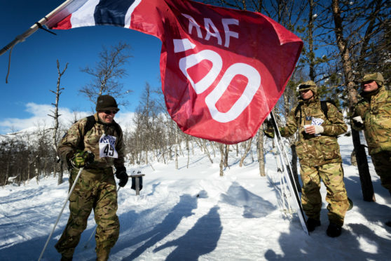The RAF100 flag is waved at the finish line of the cross-country skiing race held on the final day of Ex-WINTERMARCH as one of the skiers crosses the line.