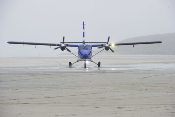 The new Twin Otter DHC6-400 aircraft taxiing along the beach runway on Barra, 19 June 2015.  Credit: Stuart Nicol Photography 2013.