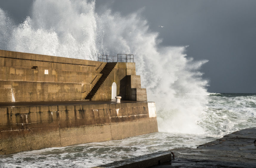 Picture by JASON HEDGES     Pictures show waves battering Lossiemouth harbour wall today due to the excessive winds .