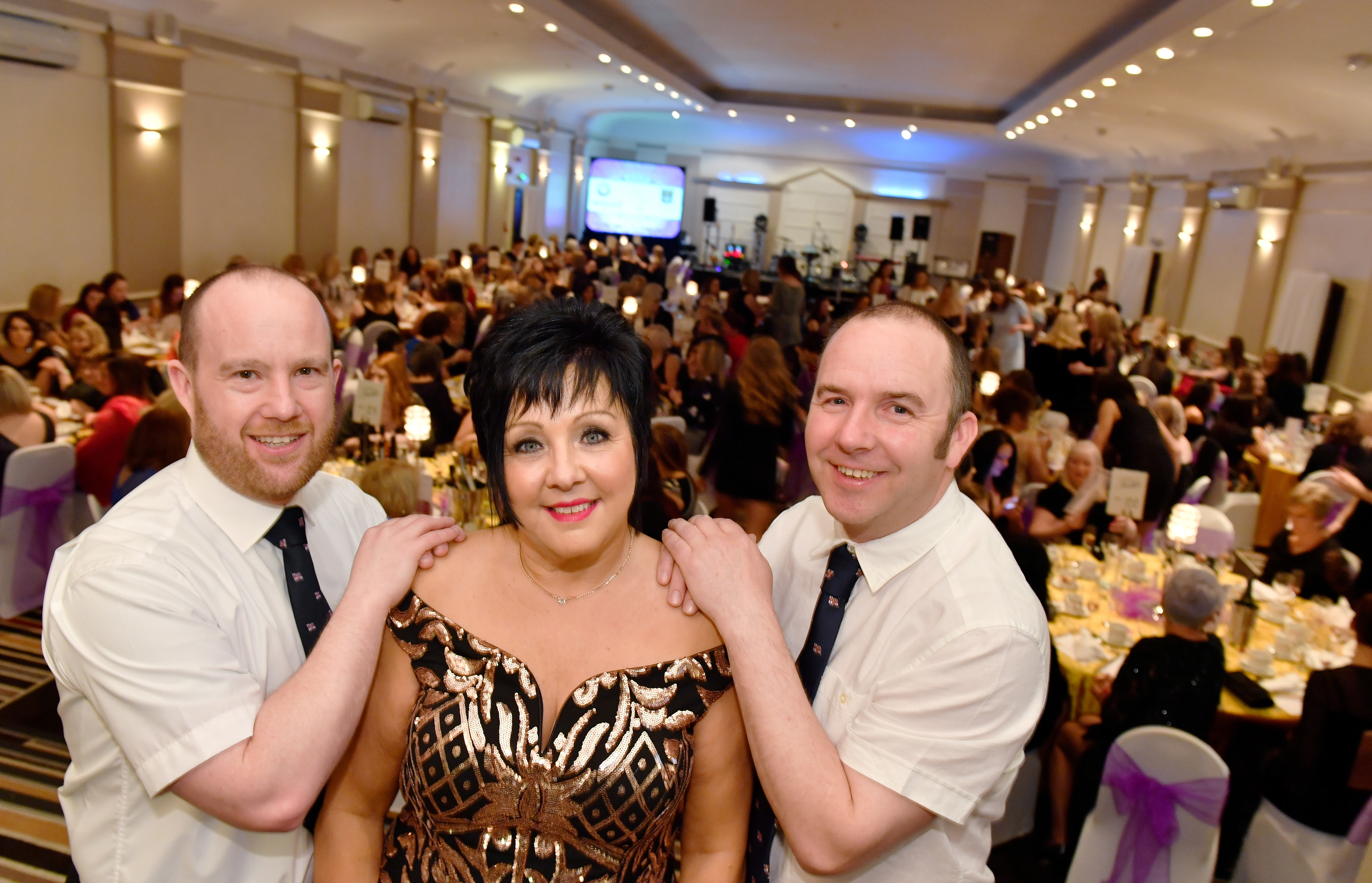 Audrey Wood who with her annual Ladies Glamour Glitz and Bubbles afternoon has raised £162,000 to date for the RNLI.    Audrey is pictured with RNLI crew members Deputy Coxwain Robbie Coull (left) and ILB Helm Bruce Finnie at her latest event at the Douglas Hotel.     Picture by Kami Thomson    03-03-18