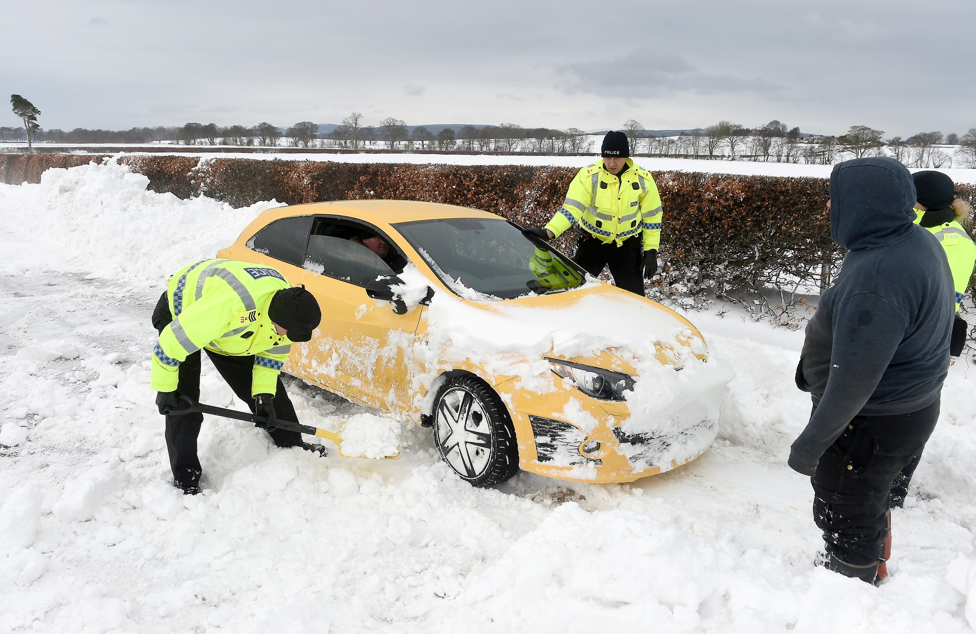 Police and farmers with heavy machinery recover cars and clear deep drifts on the road between Arabella and Hill of Fearn in Easter Ross yesterday morning. Picture by Sandy McCook.