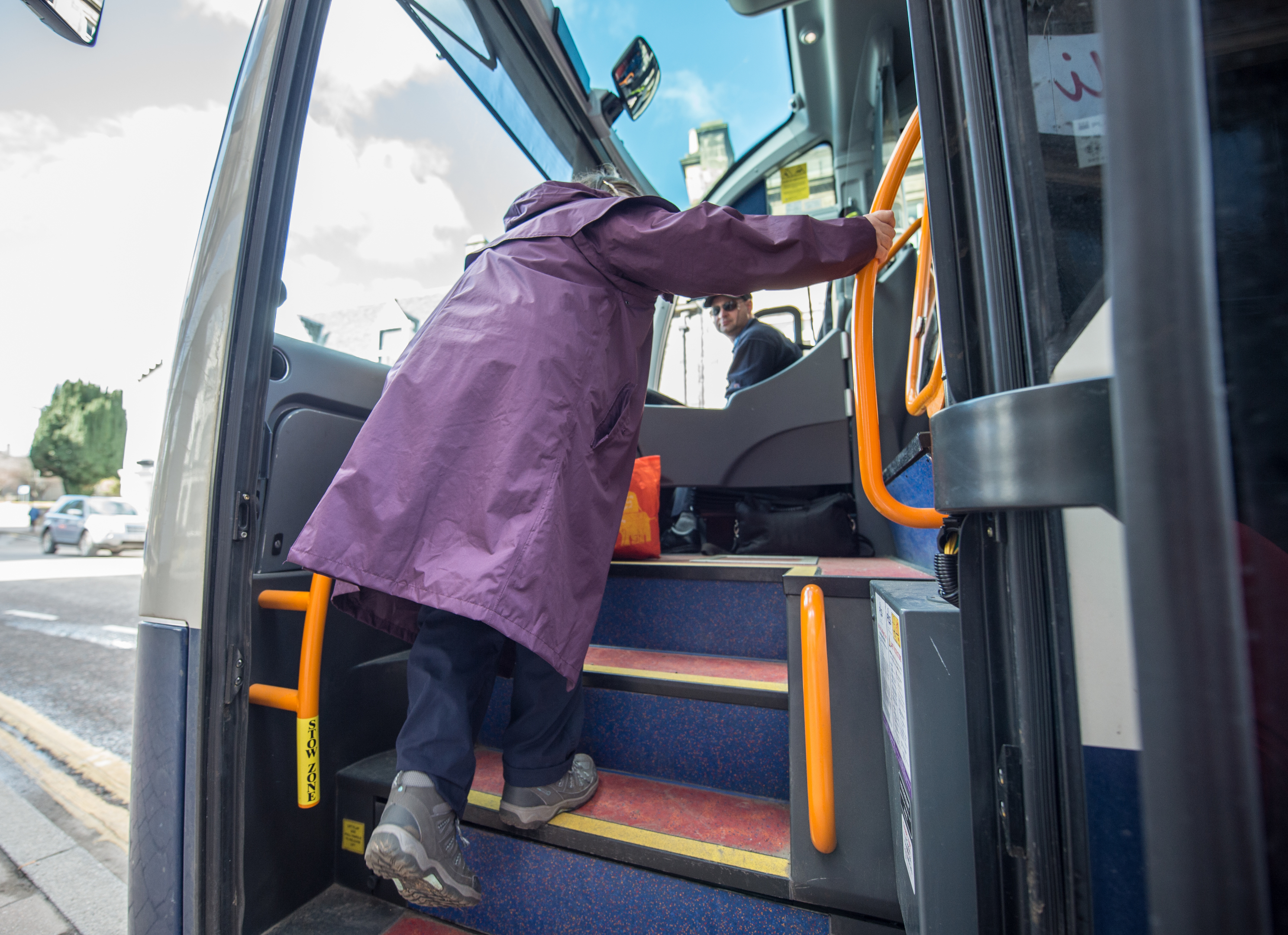 A passenger climbs the bus after boarding in Forres