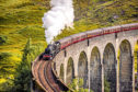 Glenfinnan Railway Viaduct in Scotland with the Jacobite steam train passing over.