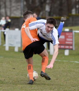Nairn County's Max Ewan is upended by Rothes' Blair Maclennan.