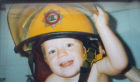 Kobi Poole in his dad's helmet as a youngster.