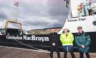 Stuart Craig, left, and Gordon Law of the Clyde River Steamer Club with CalMac's Jonathan Davies, centre, beside the MV Eigg