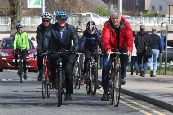 Drew Hendry MP and John Finnie MSP lead the procession of cyclists across town to the Highland Council HQ.