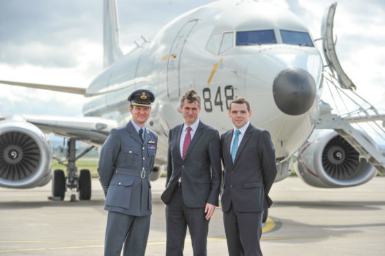 Defence Minister Gavin Williamson, pictured centre, and the new Posieidon P8 that will come into RAF service. Also pictured: Station Commander Jim Walls, left, Moray MP Douglas Ross, right.