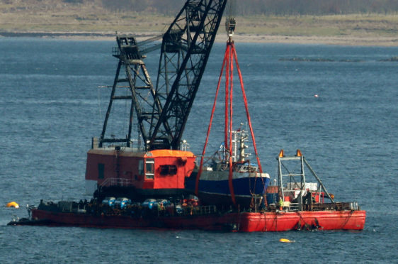 The Nancy Glen fishing trawler sits on a barge on Loch Fyne after its recovery