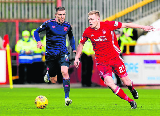 Aberdeen's Sam Cosgrove (right) skips away from Hearts' Aaron Hughes