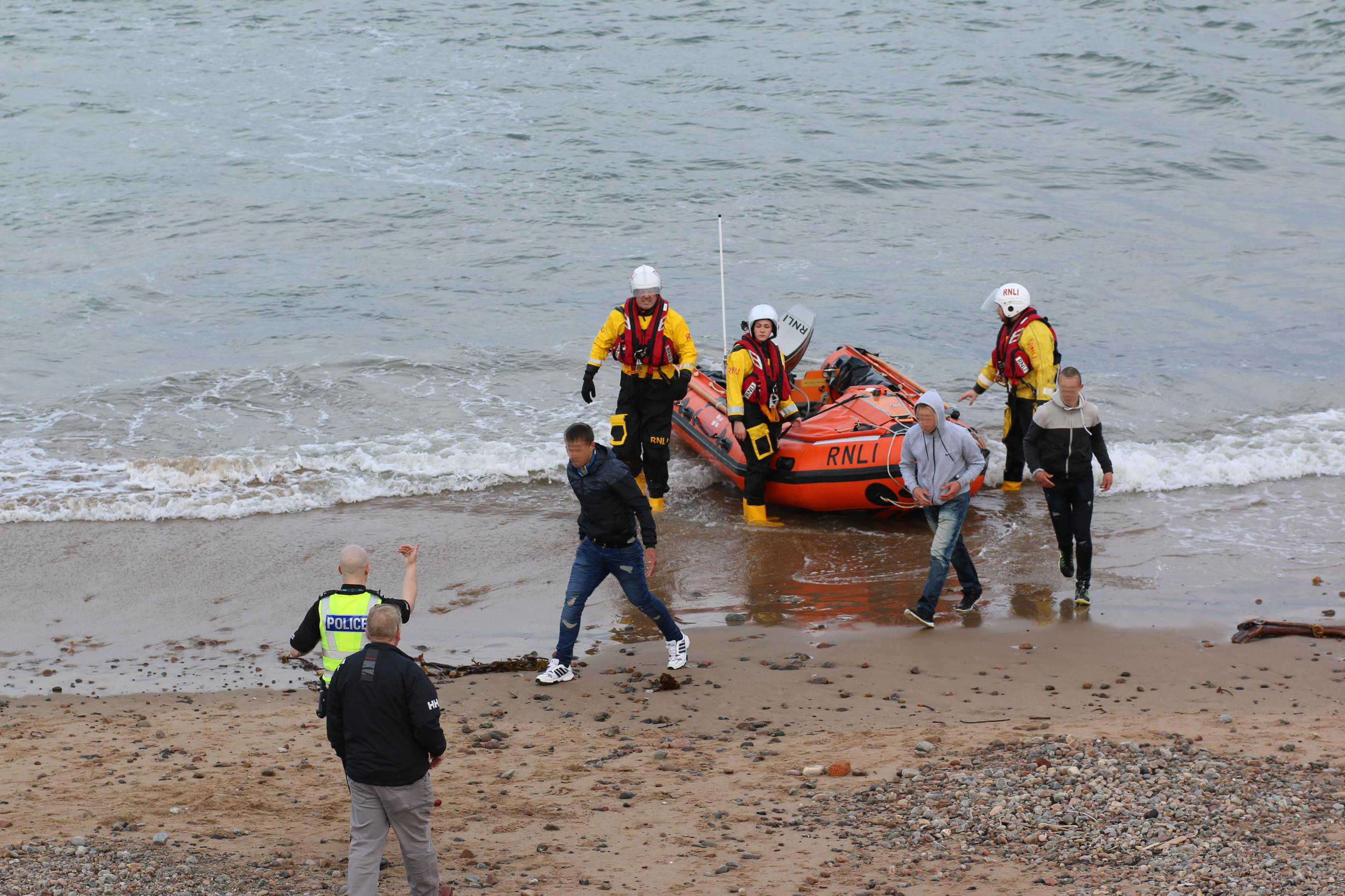 The three men were brought ashore to the beach where they were met by police.