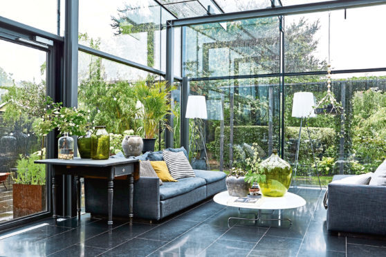 A contemporary glass and steel extension designed by a Swedish architect to sit among the lush green garden foliage that surrounds it