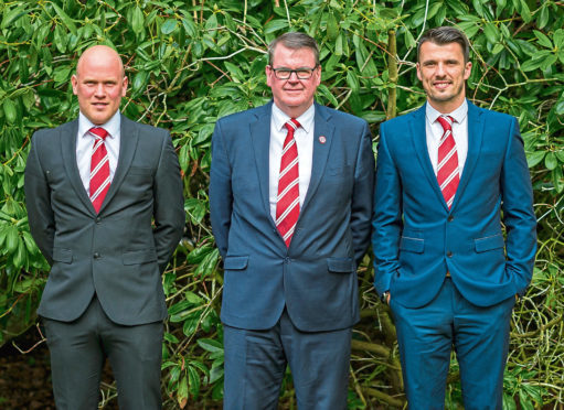 Brora coach Craig Campbell, Powrie and manager Steven Mackay.