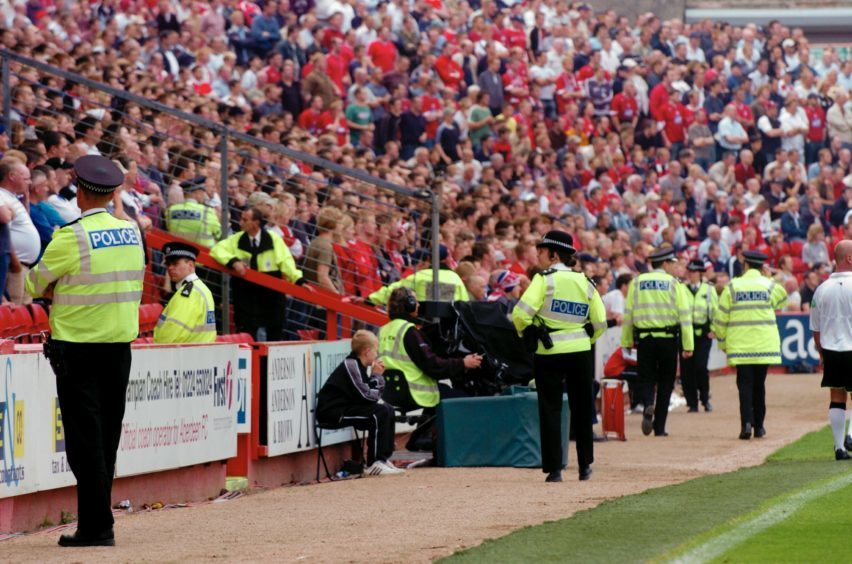 Police patrol the south stand at Pittodrie.