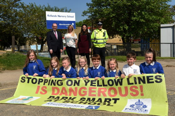 Colourful banners being displayed outside schools where there are parking problems. Picture of (L-R) Ron McKail, Joanna Stewart, Sally Davis, PC Steve Middelton and pupils from Kellands School.  Picture by KENNY ELRICK     23/05/2018