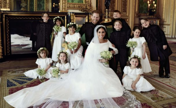 Prince Harry and Meghan Markle surrounded by bridesmaids and page boys after their wedding.