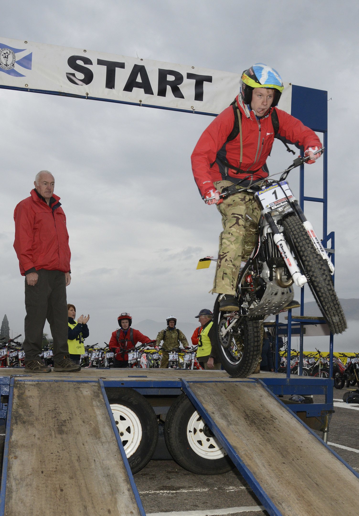 Army rider Stuart Mack leaps from the starting podium flagged off by Lt Col. (ret) Mike Tizzard of the Army Motorcycle Club. Picture: Iain Ferguson.