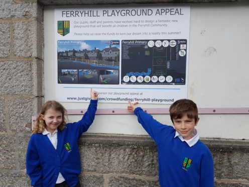 Primary four pupils Elizabeth Martin and Scott Condie look at the plans for the revamped playground at Ferryhill School.
