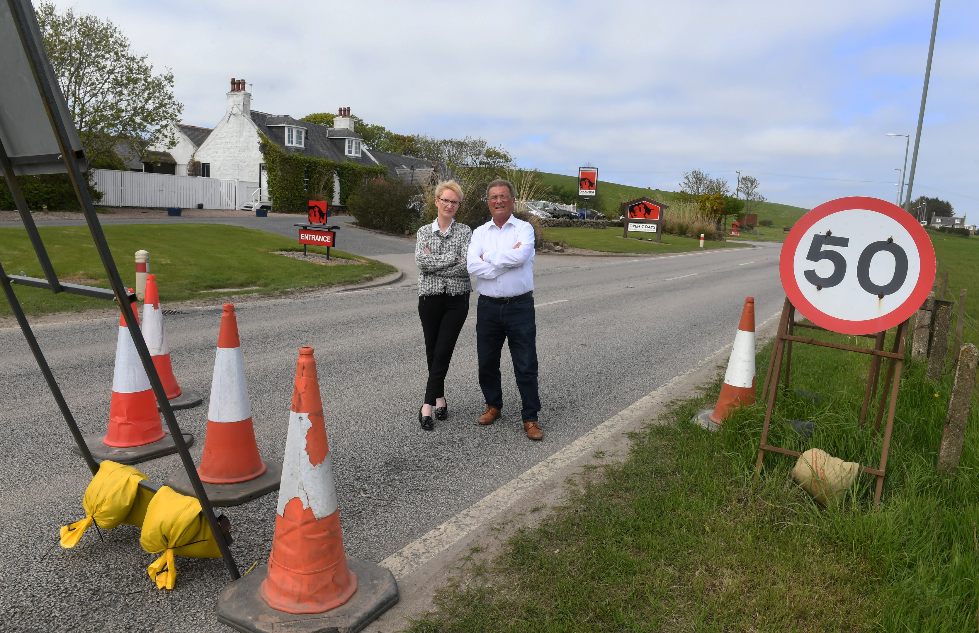 Pictured are Mandy Davidson a director of the Cock and Bull and Rodger Morrison the owner having a chat on the old A90 by the restaurant. The restaurant is losing £700 a day and the AWPR are not putting signage up  to the restaurant. Pic by Chris Sumner 23/5/18